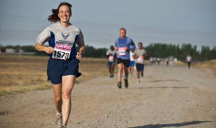 woman smiling running a sprint finish on a dusty path