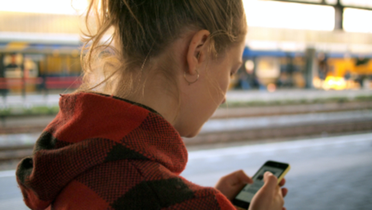 person using phone at train station by Daria Nepriakhina on Unsplash
