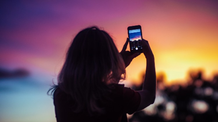 person talking a photo of sunset by Vitaly Sacred on Unsplash