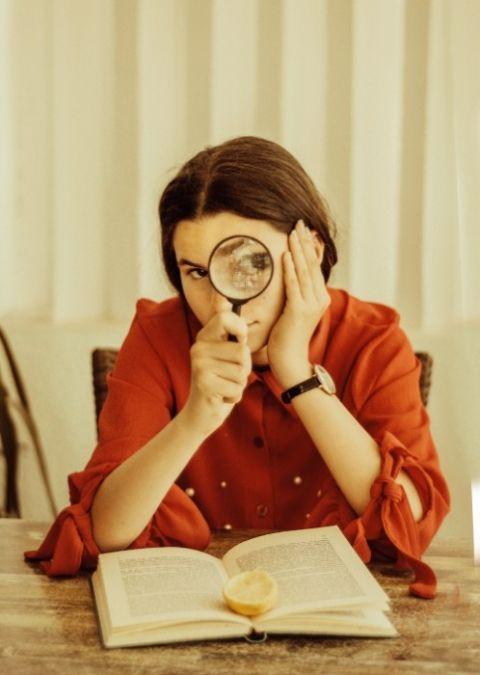 woman with magnifying glass and a book by houcine ncib
